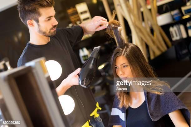 jovem mulher recebendo novo penteado no salão de cabeleireiro - penteando - fotografias e filmes do acervo