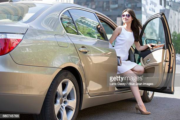 Young woman getting out of a car