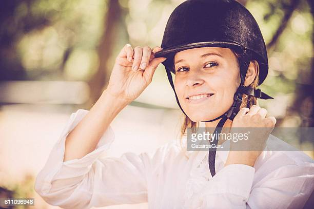young woman getting read for a horseriding - riding hat stock pictures, royalty-free photos & images