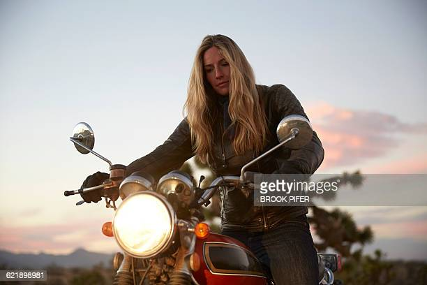 young woman getting ready for motorcycle ride - motorcycle stock pictures, royalty-free photos & images