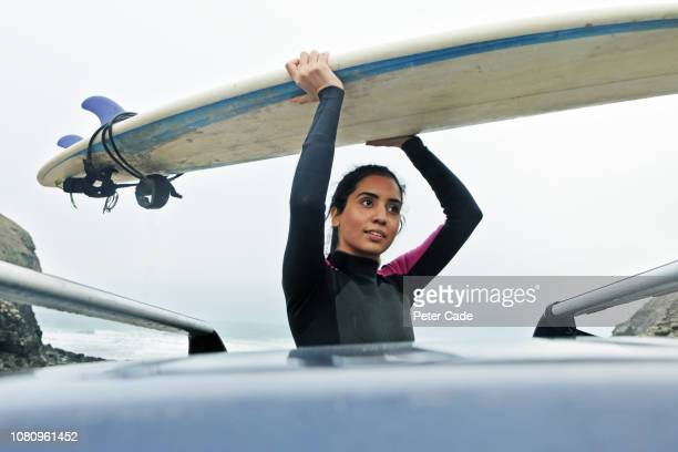 Young woman getting surfboard off car roof
