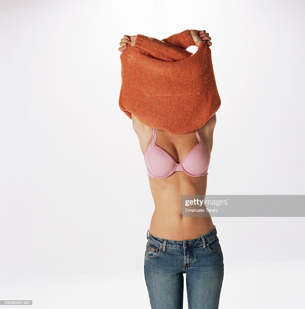 young woman getting undressed pulling sweater over head rear view