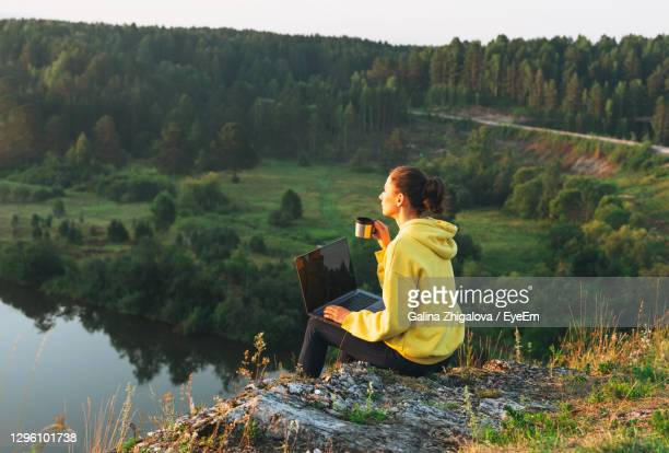 young woman girl traveler freelancer in yellow hoodie with opened laptop looking at sunrise - idyllic stock pictures, royalty-free photos & images