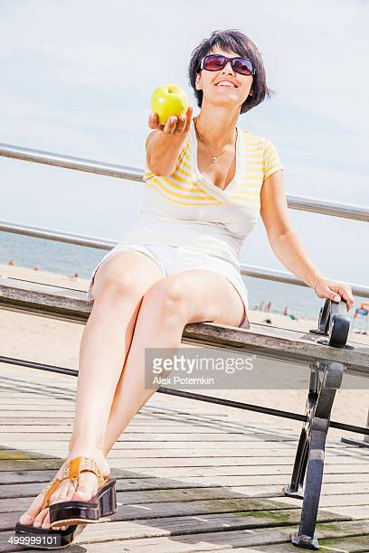 Young woman give the apple to somebody