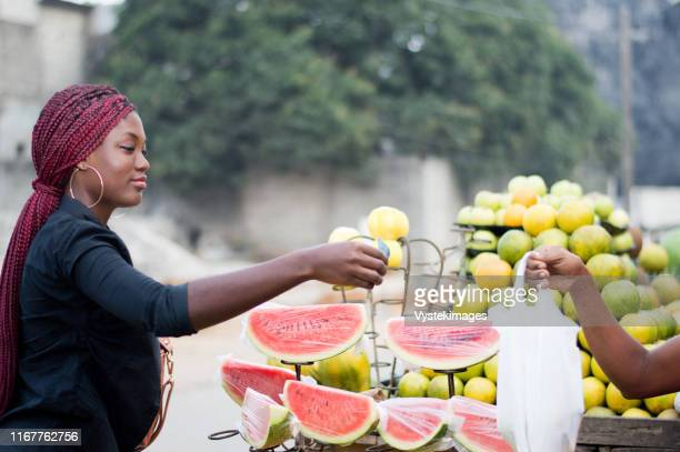 young woman gives a banknote to the vendor at street fruit market. - côte d'ivoire stock pictures, royalty-free photos & images