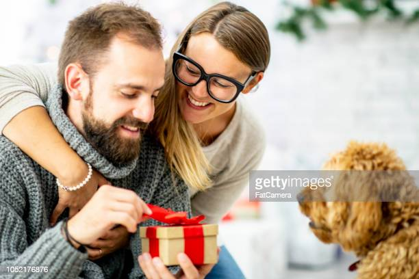 young woman gives her partner a wrapped gift - dog knotted in woman stock pictures, royalty-free photos & images