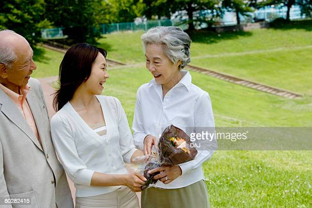 Young woman giving a flower bouquet to senior woman, smiling