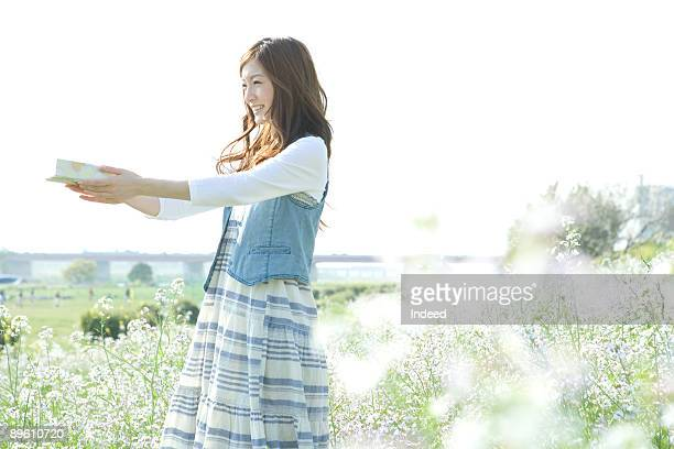 Young woman giving a gift box on field