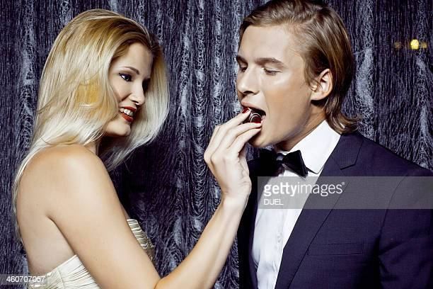 Young woman giving chocolate to boyfriend