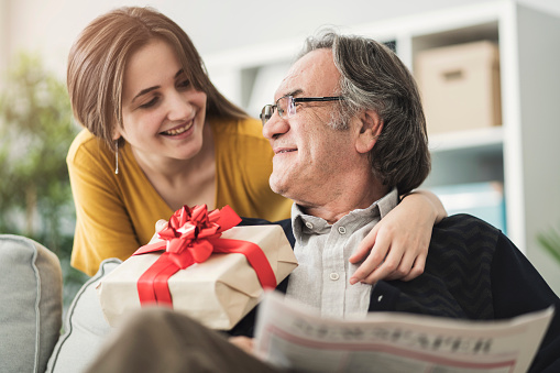 Young woman giving gift her father 1005890028