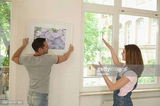 Young woman giving guidance to man adjusting picture on wall