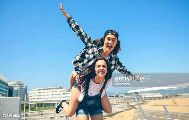young woman giving her friend a piggyback ride on roof terrace - piggyback stock pictures, royalty-free photos & images