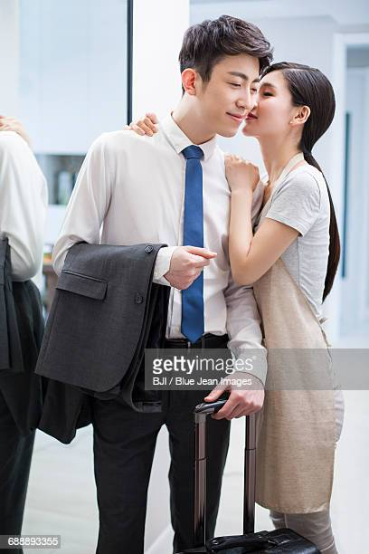 Young Woman Giving Her Husband A Goodbye Kiss Stock Photo - Getty Images