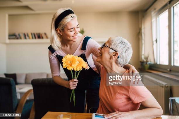 young woman giving her mother flowers - mothers day stock pictures, royalty-free photos & images