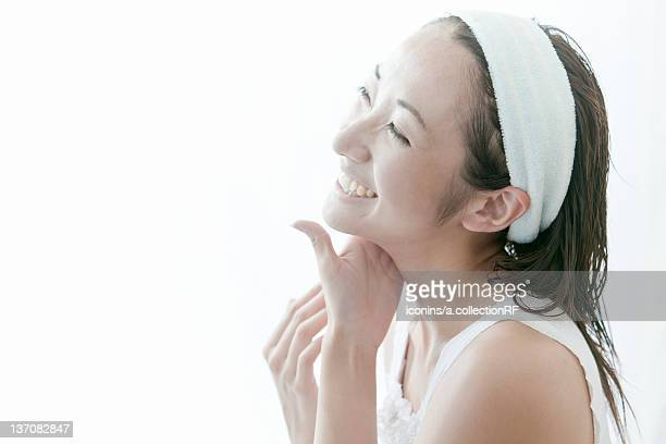 Young woman giving herself a facial massage, Tokyo Prefecture, Japan