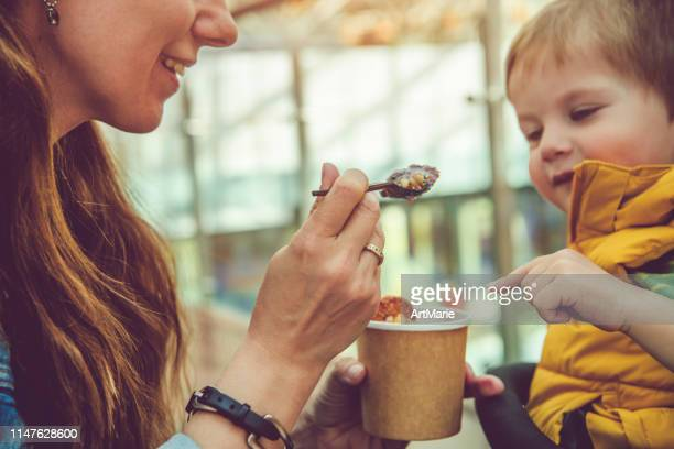 giovane donna dando a suo figlio sano gelato arrotolato o yogurt con frutta o bacche, biscotti, caramelle e menta - coppa gelato foto e immagini stock
