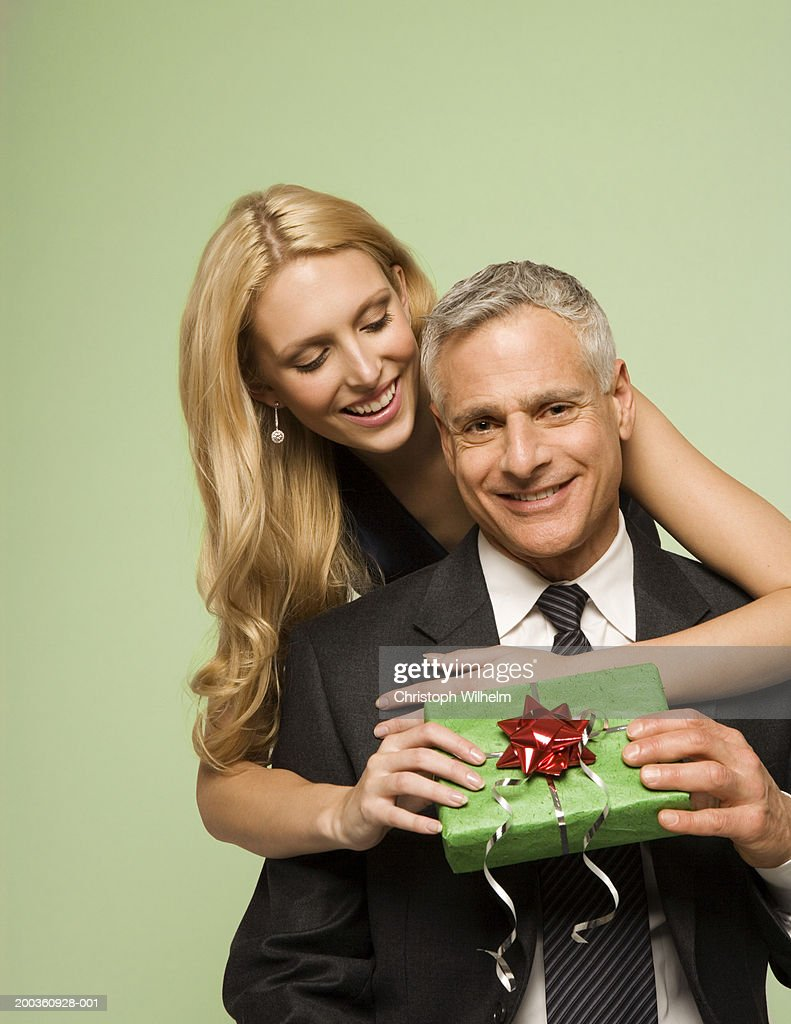 Young woman giving mature man Christmas present : Stock Photo
