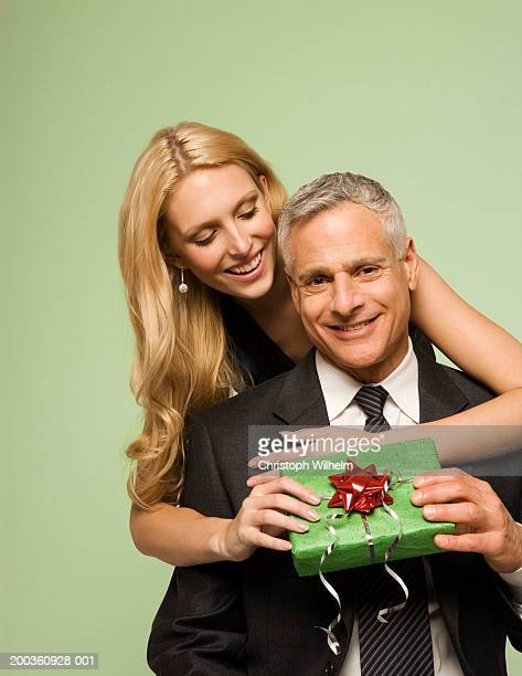 young woman giving mature man christmas present - sugar daddy stock photos and pictures