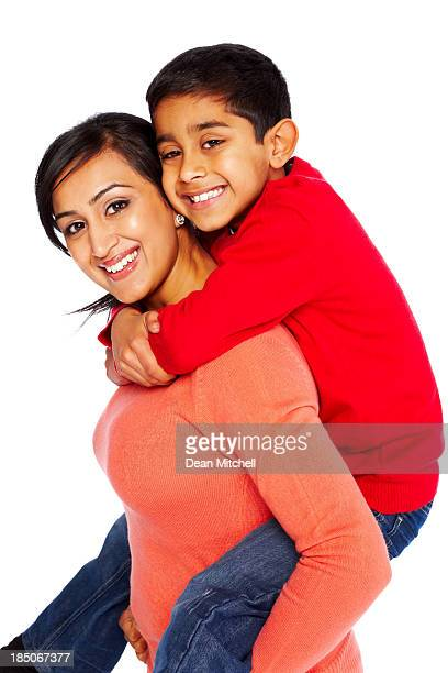 Young woman giving piggyback ride to her son