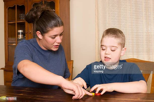 Young woman giving small boy therapy for behavior analysis
