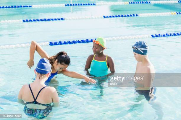young woman giving swim lessons to multi-ethnic group - freestyle swimming stock pictures, royalty-free photos & images