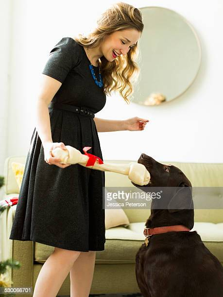 Young woman giving to dog Christmas present