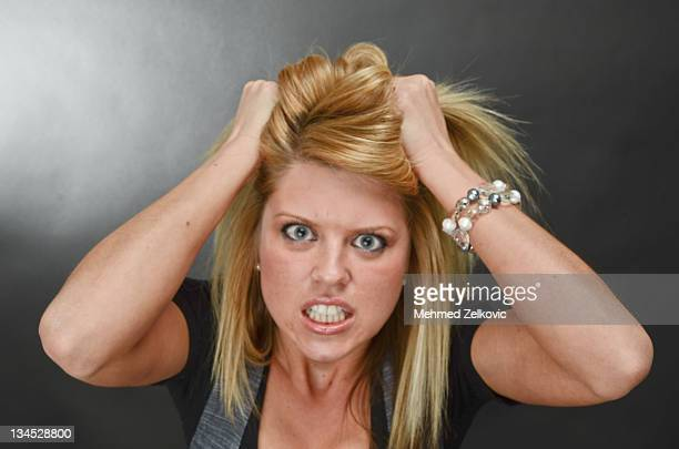 Young woman going crazy angry pulling her hair