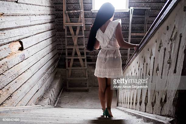 Young woman going down staircase