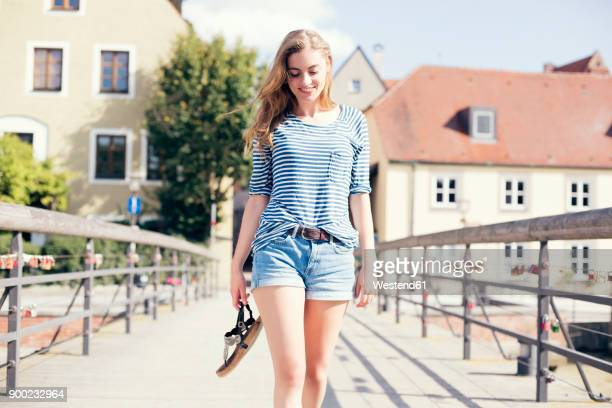 young woman going on bridge, holding her shoes - sandale stock-fotos und bilder