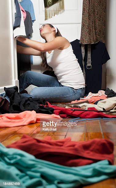 Young woman going through her closet