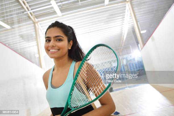 Young woman going to play squash