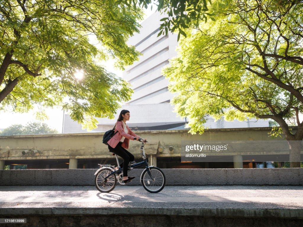 Jeune femme allant travailler à vélo : Photo