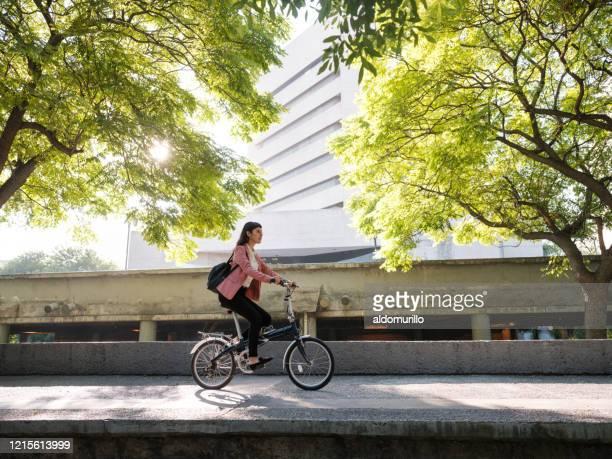 jeune femme allant travailler à vélo - city life photos et images de collection