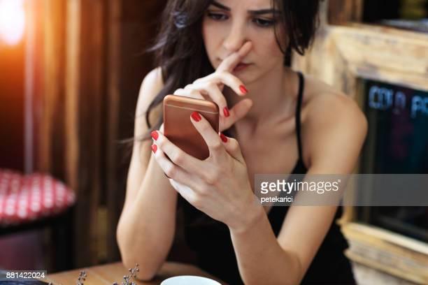 Jeune femme eu mauvaises nouvelles avec son téléphone intelligent