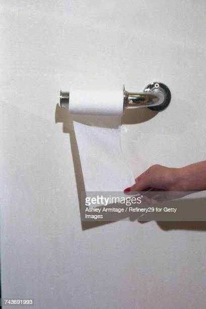 young woman grabbing toilet paper - 67percentcollection stockfoto's en -beelden