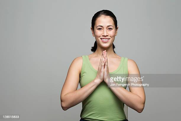 Young woman greeting with folded hands