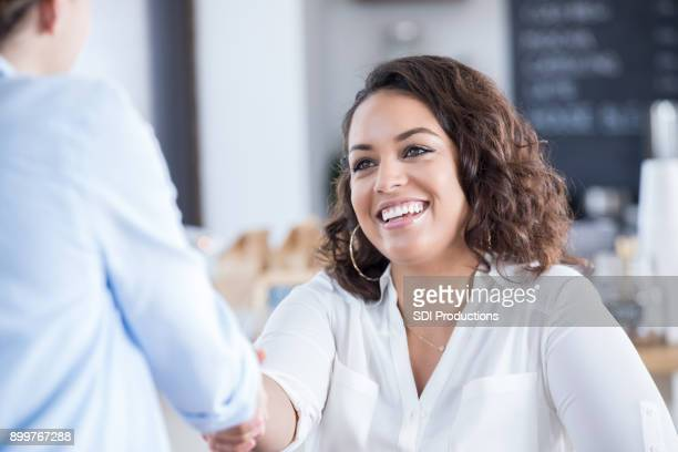 young woman greets colleague in coffee shop - bonding stock pictures, royalty-free photos & images