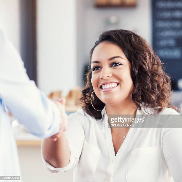 young woman greets friend in coffee shop - one young woman only stock pictures, royalty-free photos & images