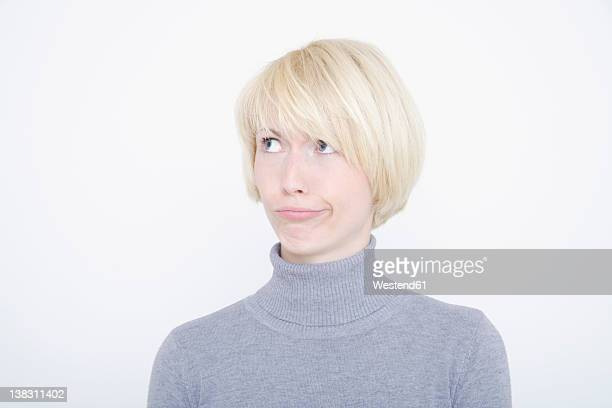 young woman grimacing against white background, close up - turtleneck stock pictures, royalty-free photos & images