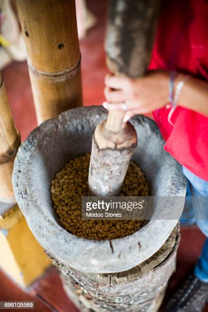 A young woman grinds coffee using an old technique while working on a coffee farm in rural Colombia.