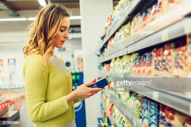 young woman groceries shopping in local supermarket. - dranken en maaltijden stockfoto's en -beelden
