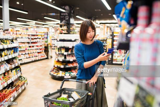 young woman grocery shopping - jgalione stock pictures, royalty-free photos & images
