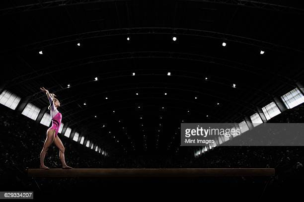 a young woman gymnast performing on the beam, balancing on a narrow piece of apparatus. - balance beam stock pictures, royalty-free photos & images