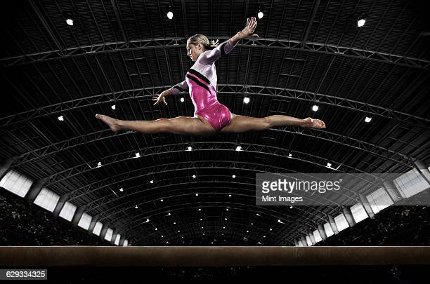 a young woman gymnast performing on the beam, balancing on a narrow piece of apparatus. - gymnastics stock pictures, royalty-free photos & images