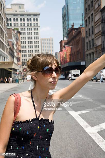 a young woman hailing a taxi, brooklyn, new york - femme poil photos et images de collection