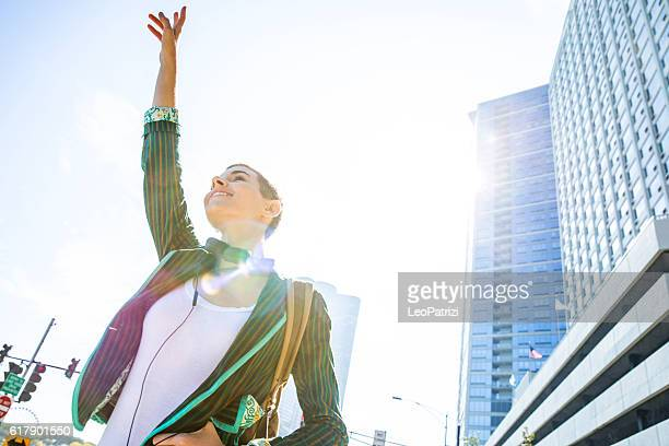 Young woman hailing in downtown Chicago
