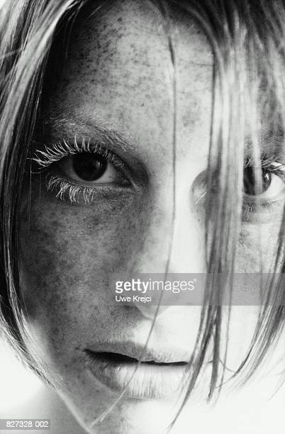 Young woman, hair falling over eyes, portrait (B&W)