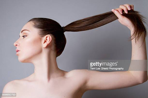 Young woman, hair in ponytail, pulling hair in upward direction