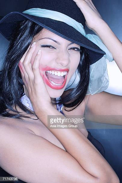 Young woman, hand on face, mouth open, lipstick smeared