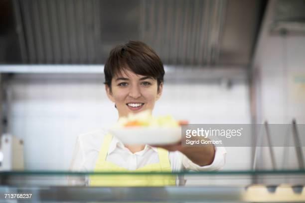 young woman handing food to customer, in fast food shop - sigrid gombert stockfoto's en -beelden